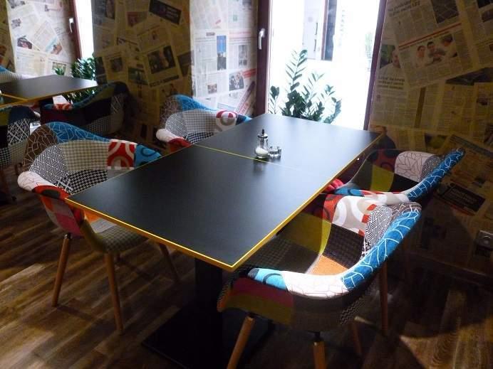 K pestrobarevným křeslům se hodí jednoduché černé stoly. Foto: Kristýna Hortvíková