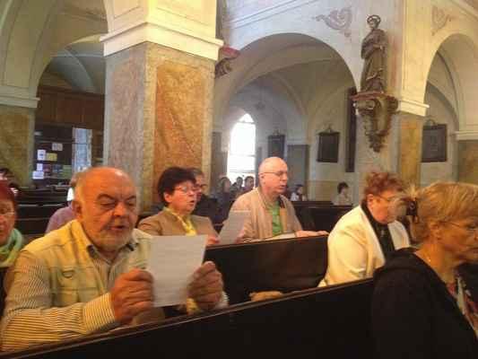 103 lidé v kostele zpívají.